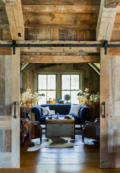 Navy blue sofa in an all-wood cabin living room with sliding living room doors. Refreshing in its simplicity, rustic style highlights natural beauty and a rugged, resilient spirit as reflected in these rustic living room designs. Rustic Interiors, Blue Interiors, Log Homes, My Dream Home, Dream Barn, Living Room Designs, House Ideas, House Design, Architecture