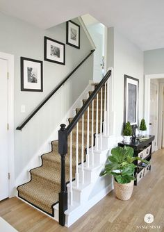 White Painted Staircase Makeover with Seagrass Stair Runner. Full step by step tutorial from removing the old carpet to staining the banisters, to installing the stair runner. Gorgeous!