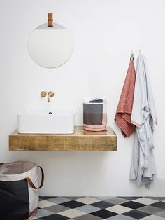Wood floating vanity and white vessel sink. Gold faucet.
