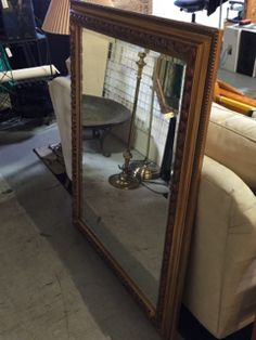 LARGE ENTRYWAY OR HALL MIRROR WITH GILT FRAME AND BEVELED GLASS. THE RAISED SCROLLWORK HAS TOUCHES OF RED. EXCELLENT CONDITION. 48H X 37W