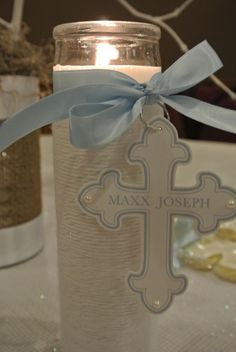 Tall candle, white twine, personalized cross paper, ribbon, and silver ring. Easy decoration!