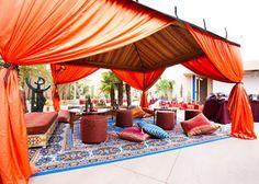 Lavish orange Moroccan tent with lush rugs and Indian decor