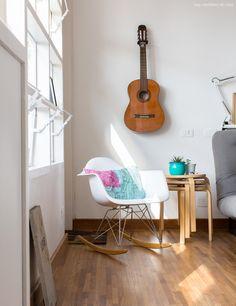 Cadeira eames, violão pendurado na parede e bancos empilhados que servem como mesinha lateral.