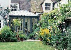 petite-veranda-victorienne-en-noir-qui-donne-sur-un-joli-jardin-magnifique-vitrage-gothique