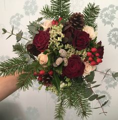 Winter wedding bridesmaid bouquet with Red and cream roses, pine cones, bouvardia and hypericum with eucalyptus, ivy and pine foliage