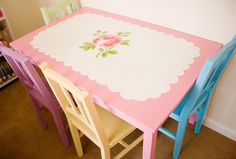 A plain wooden dining table and chairs painted with inspiration from Cath Kidston plates - scalloped edge design with rose centre on the table, & the chairs are all different pastel shades.