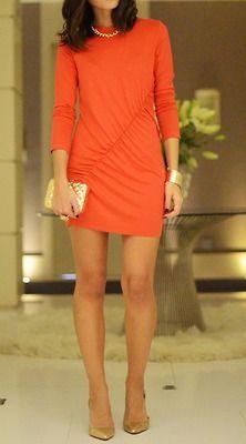 Vestido de coctel naranja con complementos dorados.