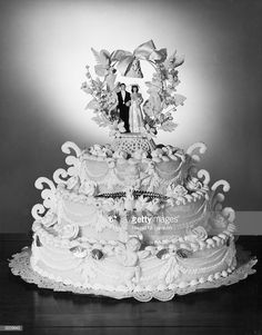 Still-life of a three-tiered wedding cake decorated with figurines of a bride and groom standing beneath a wreath on the top layer. Mini Wedding Cakes, Amazing Wedding Cakes, Wedding Cupcakes, Amazing Cakes, Extravagant Wedding Cakes, Elegant Wedding Cakes, Elegant Cakes, Fountain Wedding Cakes, Vintage Cake Toppers