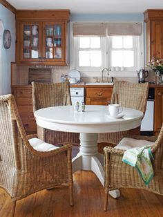 Love the contrast of natural wood, white table and wicker chairs.