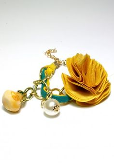 Bracelet with yellow flower, pearl and orange stone on a gold chain with interleaved decorative green and yellow strap. It is perfect to spring and summer stylizations. Very girly and positive.