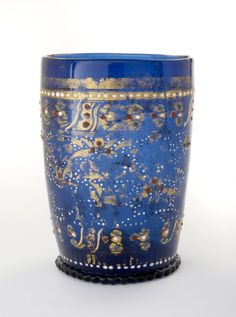 cylindrical with denticulated base-ring and kick in base; decorated with broad band of gilt foliate design bordered by further gilt bands and white enamel beading; whole sprinkled with white dots and clusters of red and blue dots. Murano Glass, Venetian Glass, Antique Glass, Gold Glass, Glass Art, History Of Glass, Glass Gemstone, Drinking Glass, Dark Ages