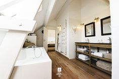 Attic bathroom features sloped ceiling framing skylight over modern freestanding tub across from weathered oak double vanity with shelves topped with honed ...