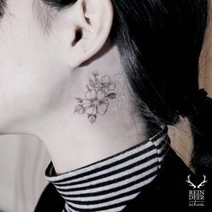 Cherry blossoms tattoo behind the left ear.