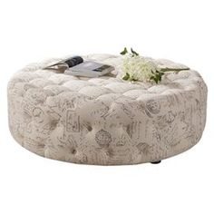 """Eucalyptus wood cocktail ottoman with tufted linen upholstery showcasing a French script motif.    Product: OttomanConstruction Material: Solid eucalyptus wood, linen and polyurethane foamColor: CreamFeatures:Button-tuftedScript detailsDimensions: 15.75"""" H x 47"""" DiameterCleaning and Care: Spot clean only"""