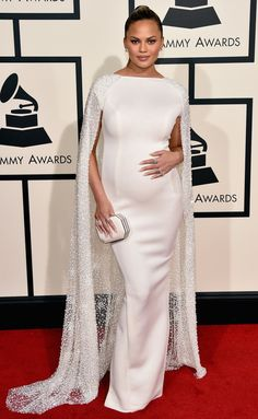 Chrissy Teigen showed off her burgeoning bump in a stunning white gown with an embellished cape, looking every bit a glowing new mom.