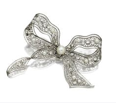DIAMOND AND PEARL BOW BROOCH, CIRCA 1910.  The ribbon bow of lattice motif set throughout with 70 old European-cut, old-mine and single-cut diamonds weighing approximately 6.40 carats, the center accented with a natural pearl measuring approximately 9.8 by 9.4 mm., further decorated with 15 smaller pearls, mounted in platinum.