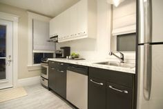 Sleek and modern kitchen with new cabinets, counters, floors and exterior door. #IncomeProperty