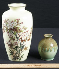 HAND PAINTED ENAMELED VASE WITH FLORAL DEISN, POSSIBLY CHERRY BLOSSOMS WITH A PALE YELLOW BACK GROUND. MEASURES 10IN. TALL. THE SECOND ONE, IS A BUD VASE DONE IN GREENS AND GOLD TONES. THIS STANDS AT 5 IN.TALL.