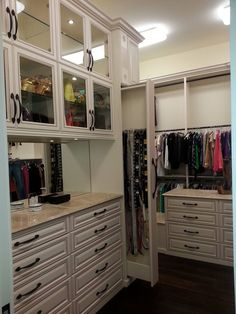 This gorgeous walk-in features Oil Rubbed Bronze hardware, glass-framed cabinets, raised panel drawer faces and concealed storage for belts.  Designed by professional designer Jeanne Hessen  Learn more here: https://www.closetfactory.com/custom-closets/ Wardrobe Closet, Closet Space, Walk In Closet, Dressing Table Room, Wardrobe Cabinets, Raised Panel, Custom Closets, Closet Designs, Custom Cabinets