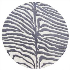 Decorate your home with a piece of the African safari with this wild round area rug. Handmade of plush New Zealand wool, this fierce area rug features a safari grey and off-white zebra-stripe pattern that is sure to embolden your decor.