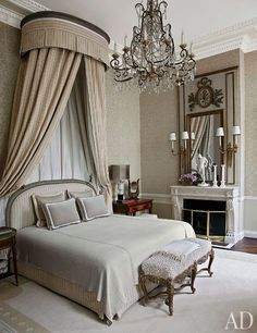 The bed in the master suite of a Paris apartment by Jean-Louis Deniot is highlighted by an 18th-century corona and an 1880s Italian chandelier.