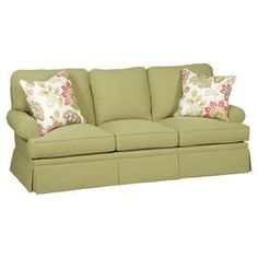 """Skirted sofa with basil green upholstery and 2 floral-print throw pillows. Made in the USA.     Product: SofaConstruction Material: Fabric and foamColor: BasilFeatures:  Made in the USAIncludes two throw pillows Dimensions: Sofa: 35"""" H x 86.5"""" W x 38"""" D Throw pillow: 21"""" x 21"""" each"""