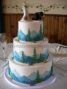 A tiered cake decorated with mountain scenery. I LOVE the cake topper! Perfect for us country girls ^_^