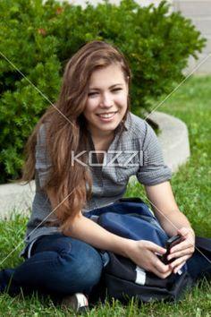 smiling teenage girl sitting in park. - Portrait of a smiling teenage girl sitting in park, Model: Cassandra Kosmayer