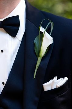 White calla lilies with looped green bear wrapped in grey-blue ribbon with the stems showing
