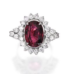 18 KARAT WHITE GOLD, SPINEL AND DIAMOND RING Centered by an oval-shaped spinel weighing approximately 7.35 carats, framed by round diamonds weighing approximately 1.30 carats