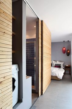 Credit:  Cladded sliding doors serve as a feature wall while concealing bathroom and utility space