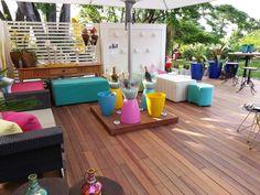 A área externa conta com piso deck, aparadores, puffs, sofás, espaço para servir bebidas, entre outros. Tudo colorido!