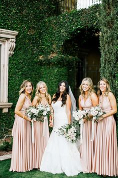 Bridesmaidsin long halter top blush pink dresses with hand-tied bouquets of blush pink roses, green leaves, hydrangrea and ivy |Feather& Twine Photography | villasiena.cc