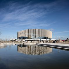 Danish firm has completed a large sporting and cultural arena in Copenhagen, featuring a glazed curtain wall wrapped in timber fins arranged to allow partial views of the interior. Building Facade, Building Design, Facade Architecture, Amazing Architecture, Circular Buildings, Round Building, Wooden Facade, Architecture Presentation Board, Mall Design