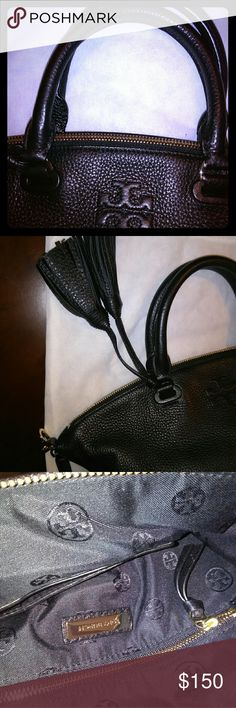 A Black Leather Tory Burch Bag Very soft Pebble leather with attached handles, tassles and detachable shoulder strap. Goldtone zipper across the top and on inside pocket. Bags