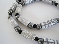 Shades of Gray is a single strand, lightweight necklace of handmade paper beads from my Pushing The Envelope series.    Paper beads made from security envelopes and gift wrap alternate with silvery gray Swarovski pearlized crystals and black satin finish seed beads. The clasp is a handmade pure silver spiral.    Dimensions:  28 1/2 Necklace  1/2 paper beads in three patterns    Your necklace comes boxed.