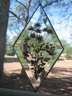This is a 4 x 7 Diamond Bevel Suncatcher. The flowers are from my garden that I have dried and pressed. Both sides are Bevels.. It is wrapped in copper foil, soldered and waxed to a beautiful shine. It has a hook for hanging and can go on a wall or in a window