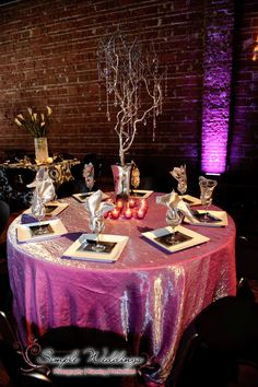 Silver tree centerpiece with hanging crystals centerpiece surrounded by votive candles.