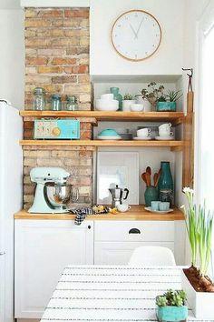 Parede de tijolos à vista na cozinha, atrás de estantes de madeira.