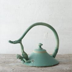 "An ornately sculpted frog supports the handle of this elegant teapot, each one hand-crafted by Utah artist Johnny Hughes and finished with a serene, blue-green glaze.- Glazed ceramic- Handmade in the USA12.5""H, 11"" diameter"