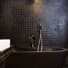 A diminutive studio is loaded with black tiles and fittings for a dramatic look.
