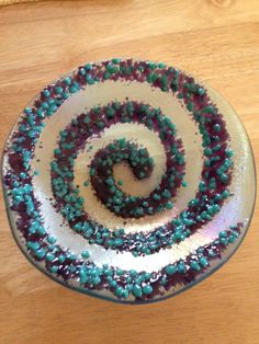 8 inch spiral bowl slumped in an organic mold.  Full fused rainbow Irrid/clear back over turquoise translucent, then soft fused med and coarse frit in two colors in a spiral pattern over base.  Printed a spiral out on the computer and laid under base, covered with glue and poured frit over then soft fused.  By Kim Natwig.