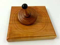 This beautiful top was wood-turned and textured from one piece of Cherry wood and is paired with a uniquely wood-turned square base that holds a shallow dish for the top to spin in. A great item for your office or home. The top is very well balanced and spins in a beautifully mesmerizing way (see picture two). While watching the top spin can be very calming and grounding, be ware of its mystical ability to draw you in and take you away from your work and stress! FINISH AND DESIGN: The top…