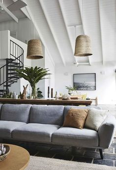 A cathedral ceiling with exposed beams painted white is the central feature of the living area and oversized rattan pendants make the most of the tall ceilings. An upholstered light blue sofa separates the dining area from the living space, and is paired with a timber coffee table and woven rug.