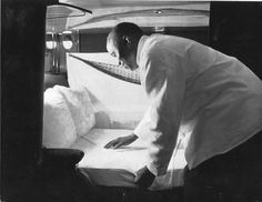 Interior view circa 1930 showing an African-American Pullman porter making down a bed in a sleeping car of an Atchison, Topeka & Santa Fe Railway passenger train. One of the most important duties of the Pullman porter was the preparation of comfortable soft riding beds for passengers. Pullman bed-making was an art and porters pride themselves on making beds that are as comfortable to sleep in as they are attractive to look at.