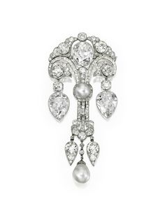 MAGNIFICENT PLATINUM, NATURAL PEARL AND DIAMOND CORSAGE ORNAMENT, CIRCA 1910 Button-shaped natural pearl 10.79 by 10.63 mm, surmounted by a cushion-cut diamond 8.67 carats, flanked by two pear-shaped diamond drops weighing 9.59 carats and 8.78 carats, completed by a natural pearl drop 11.88 by 11.69 mm. Sold US$2,042,500 at Sotheby's New York, December 2012.