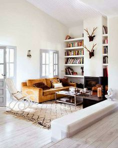 Living room: low profile gold velvet couch, white Thonet rocking chair + high storage built into nooks on the wall.