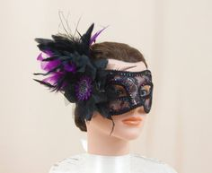 Masquerade Mask * Party Mask * Black Mask * Mardi Gras Mask * Ball Mask * Halloween Mask * Mask Centerpiece * Costume Mask  Black and Beaded Mask. We have adorned this black mask with colorful rhinestones, purple and black feather plumes and a purple embellishment. It has black ribbon that ties in the back to fasten. Color: black and purple Material: plastic mask, rhinestones and feathers measures: 10 wide and 4 high  Shipping overages will be REFUNDED.  If you would like EXPEDITED SHIPPING…