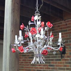 This vintage tole ceiling light fixture features a silvered metal chandelier covered in winding stems with silvered leaves and accented by fourteen red porcelain roses. Inside the ceiling cap there are two stickers E28189 and an Underwriters Laboratories, Inc., Listed Electric Fixture,