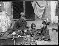 Photographer: Rabden Lepcha?, Collection: Sir Charles Bell, Date of Photo: 1920-1921, Region: Lhasa, Tibetan silversmith inLhasa engravinga charm box, or ga'u, with his two children.